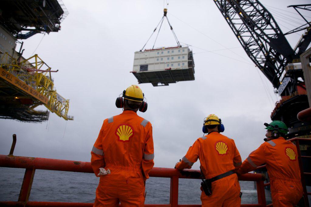 Offshore-arbeidere står spent og overvåker det tunge løftet. Foto:Ukjent